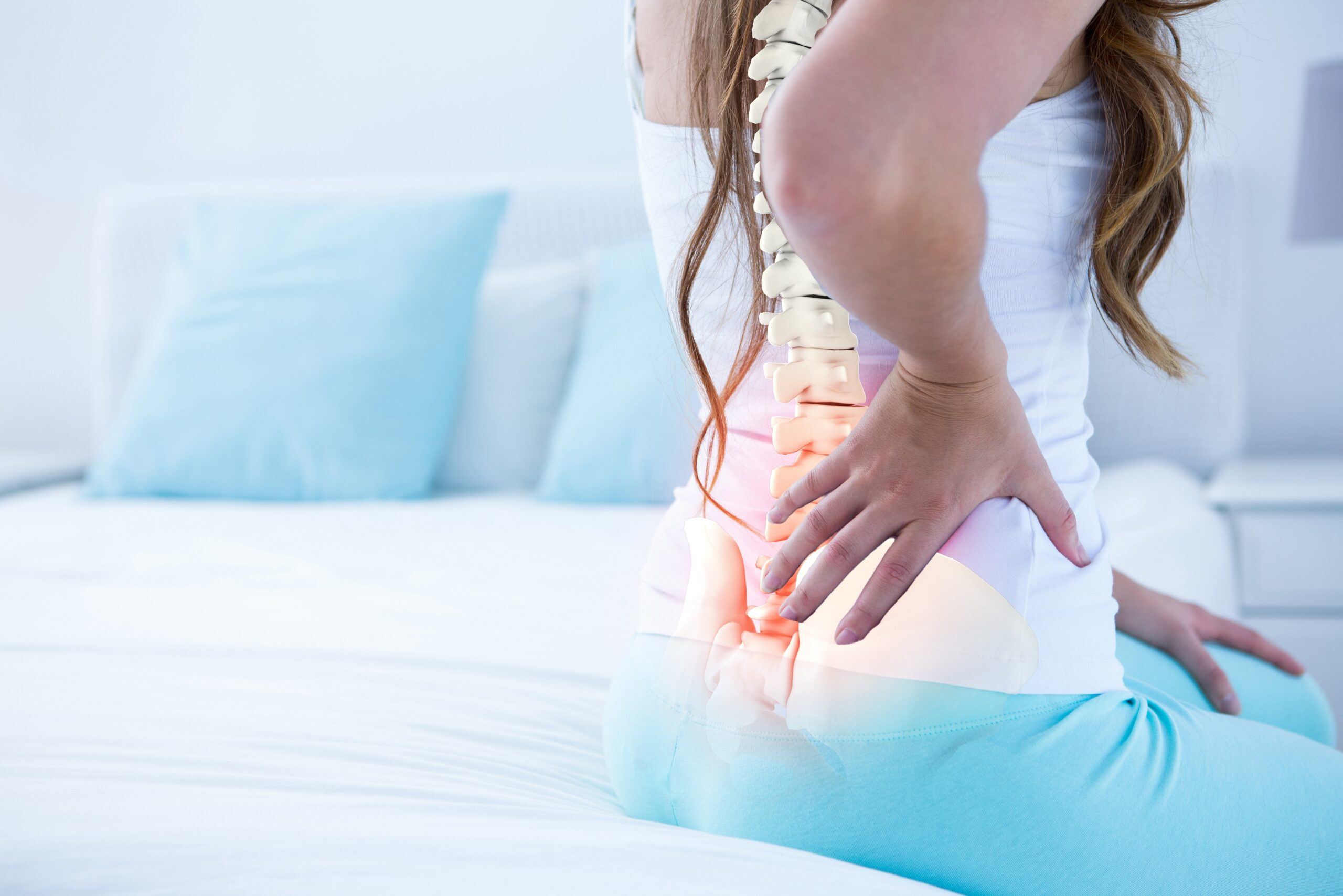 Woman showing pain in the spine, demonstrating causes of a misaligned spine