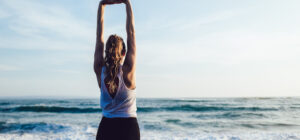 Woman with arms outstretched looking at ocean thinking about maintaining spine health